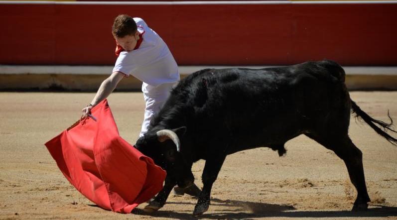 El novillero Odei Ruiz de Jimena, vestido de pamplonica, pega un derechazo a un eral de las hermanas Azcona en la Plaza de Toros de Pamplona.