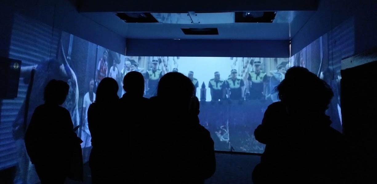 Varias personas atienden el audiovisual de la zona del callejón en la visita guiada y exposición de la Plaza de Toros de Pamplona